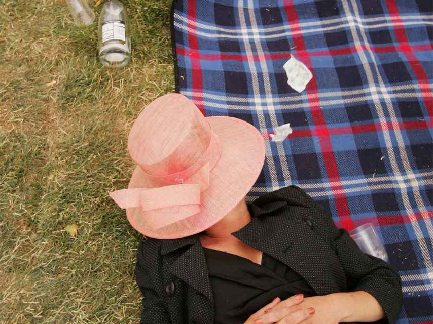 Una mujer ebria descansa en el césped en Reino Unido.